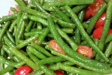 Close-up of blanched green beans and tomatoes dressed in oil and seasonings.