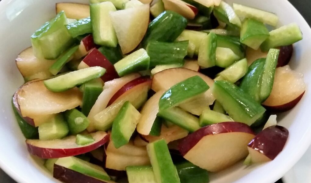Choped plum and cucumbers tossed together in a bowl