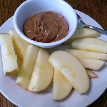 Bowl of spiced almond butter served with apple slices on a dessert plate