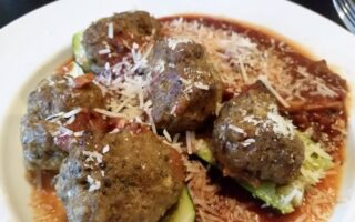 Spicy meatbals served with zuchinni and sauce in white soup bowl