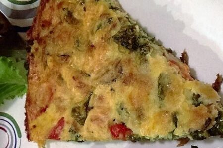 Slice of frittata on a paper plate viewed from above