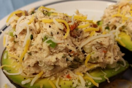 Close-up of finished cheicken salad served on two avocado halves and topped with additional shredded cheese served on a white plate