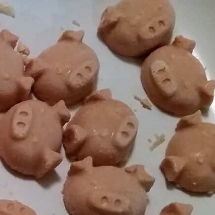 Close up of fat bombs extracted from ice trays, pig face shaped