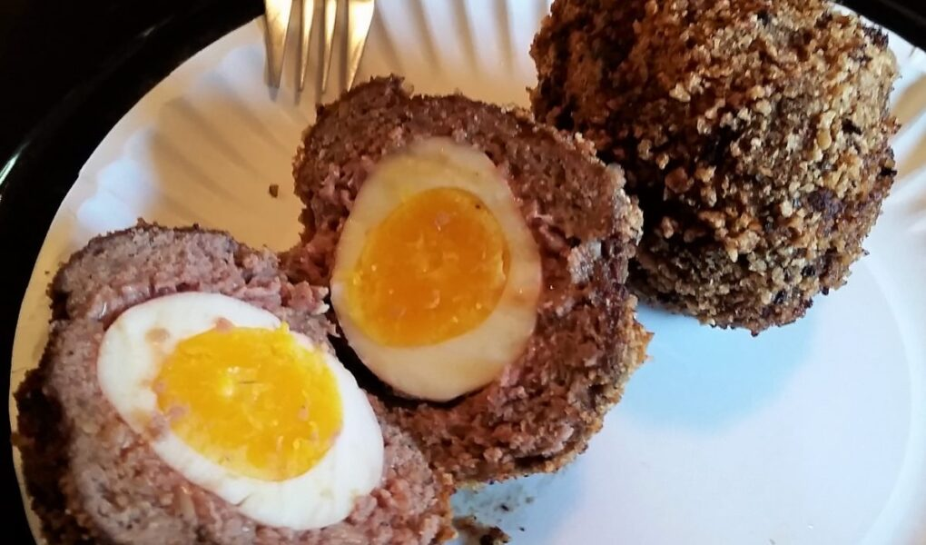 Two scotch eggs served on white paper plate, one cut in half