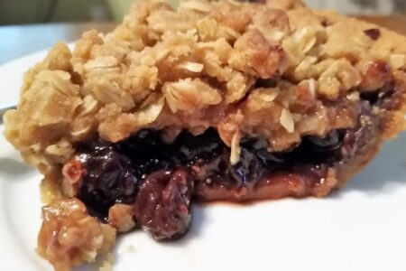 Side view of jam crumble pie on a white dessert plate