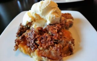 Peaches and Cream Cobbler on plate, topped with scoop of vanilla ice cream